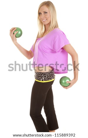 A woman working out with her green fitness balls with a smile on her face.