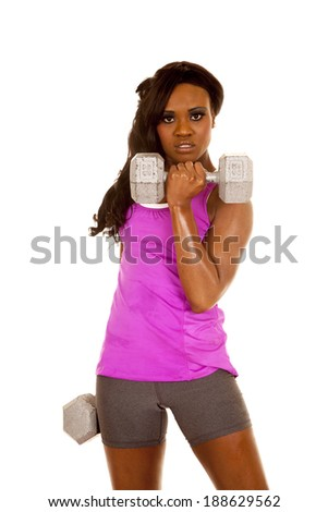 A woman working out with her weights, with a serious expression on her face - stock photo