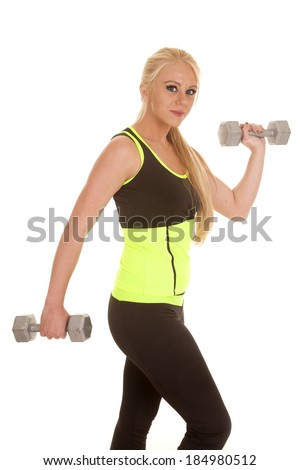 a woman working out with weights and a small smile on her lips.