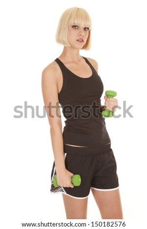 A woman working out with weights with a serious expression on her face.