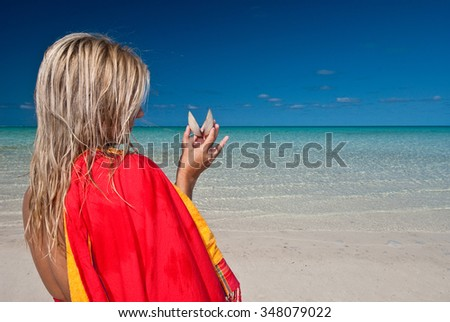 A woman wrapped in a red sarong holding a beautiful shell on a tranquil beach - stock photo