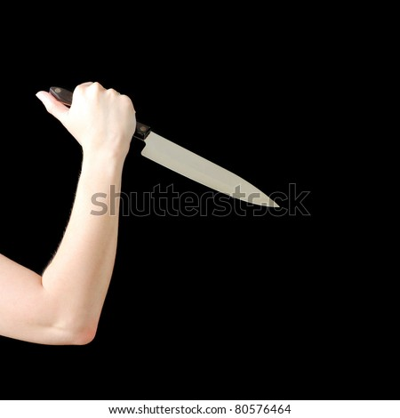 A womans arm holding a sharp knife ready to stab.