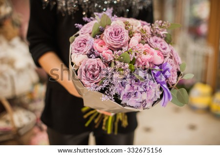 A womans hand is holding a bouquet of flowers  - stock photo