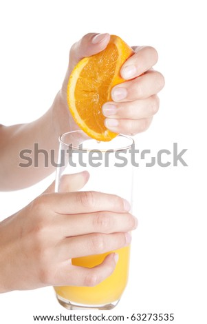 A womans hands squeezing an orange into a glass