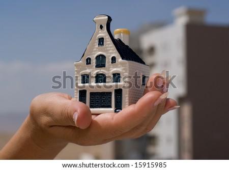 A women holding a miniature house - stock photo
