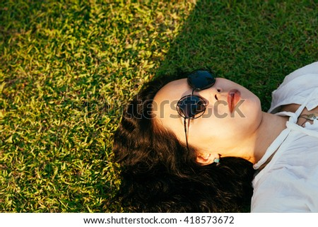 a women lying down on green grass