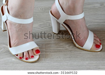 A Women's legs and a white sandals - stock photo