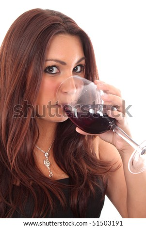 A women tasting a glass of red wine against a white background