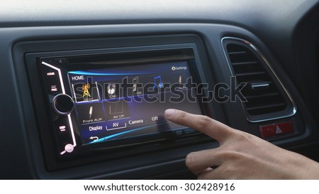 a women turn off her audio system in her car