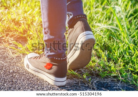 A women Walking with jeans and sneaker shoes.