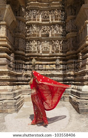 A women with her red saree blowing in the wind, walking past carvings on the walls of the Western Group of temples of Khajuraho, famous for their erotic sculptures, India. - stock photo