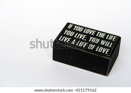 "a wood block with quote ""if you love the life you love, you will live a live for love"" on white background"