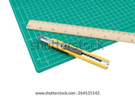 A wood ruler, cutter, cutting mat isolated over a white background - stock photo