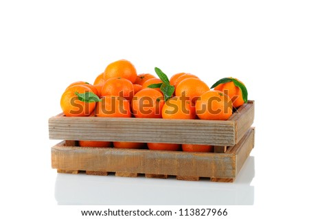 A wood rustic crate full of Clementine Mandarin Oranges. Horizontal format over a white background with reflection. - stock photo