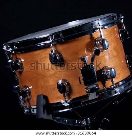 A wood snare drum isolated against a black background in the square format with copy space. - stock photo