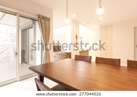 A wood table and chairs at the kitchen and living room at the daylight. - stock photo