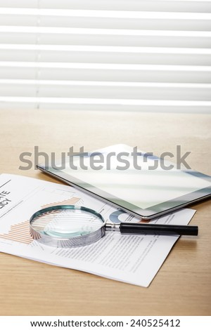 A wood working(office) table(desk) with a magnifier(reading glasses, magnifying glass[lens]), tablet pc  on the graph paper(document)s for business behind blind(rolling blind, shade).   - stock photo