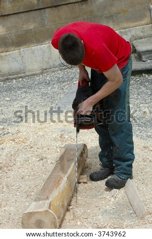 A woodcutter creating a drinking trough from a pine log with a chainsaw. Wearing no safety equipment. - stock photo