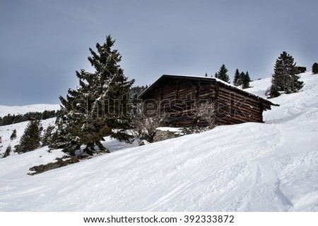 A wooden barn on the snowy slopes of the Karspitz Mountain viewed from below, Zillertal, Austria - stock photo