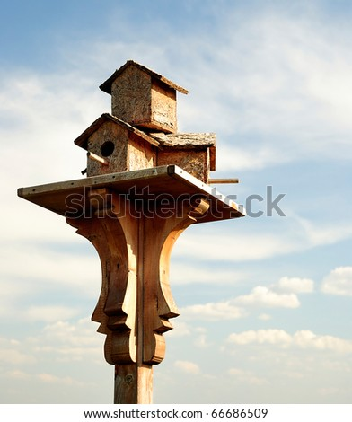 A wooden birdhouse on top of a pole with clouds in the background - stock photo