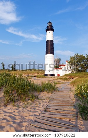 A wooden boardwalk leads from the beach to Big Sable Point Lighthouse in Ludington State Park. - Ludington Michigan - stock photo