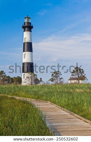 A wooden boardwalk leads through a marsh to the North Carolina's Bodie Island Lighthouse with its bold black and white stripes. - stock photo