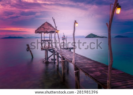 A wooden bridge leading to the sea on a beautiful sunset light. - stock photo