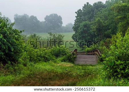 A wooden bridge on a foggy morning in Monmouth Battlefield State Park in Freehold New Jersey. - stock photo
