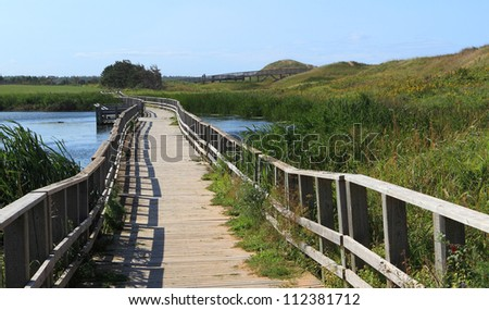 A wooden bridge over a marsh in the Cavendish Dunelands, Prince Edward Island National Park. - stock photo