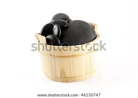 A wooden bucket filled with zen stones, isolated on white - stock photo