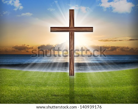A wooden cross in the sky with light rays at sunrise or sunset. - stock photo