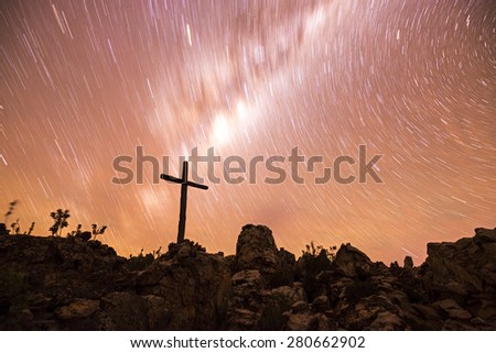 A wooden cross marks a place of memory on top of a mountain beneath the stars during this long exposure of the start trails. - stock photo