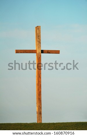 A wooden cross stands high against the blue sky.