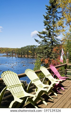 A wooden deck and chairs near a lake. - stock photo