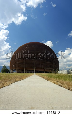 A wooden dome (the Globe of Science and Innovation at the European particle research laboratory CERN, Switzerland) rises against a blue sky with a few cumulus clouds. - stock photo