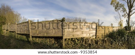 A wooden fence dividing two properties, houses yards. - stock photo
