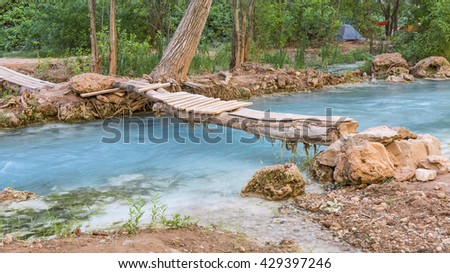 A wooden footbridge crosses Havasu Creek in the campground on the Havasupai Indian Reservation in the Grand Canyon. - stock photo