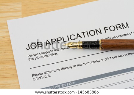 A wooden fountain pen on a wooden desk with a job application form, Applying for a job - stock photo