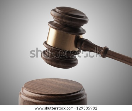 A wooden gavel and soundboard on a light grey background. - stock photo