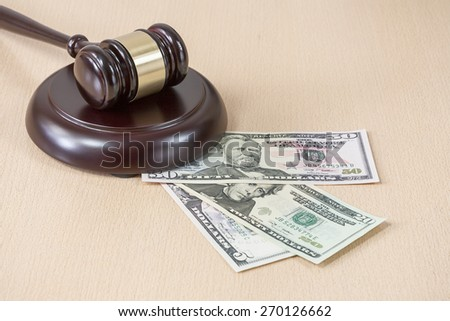 A wooden gavel on wooden table, on brown background, dollars - stock photo