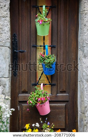 A wooden house door decorated with three colorful metal pots (with carved floral pattern)  with fuchsia flowers. Historic town Moncontour. Brittany, France - stock photo