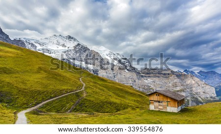 A wooden house with a beautiful mountain range in the background - stock photo