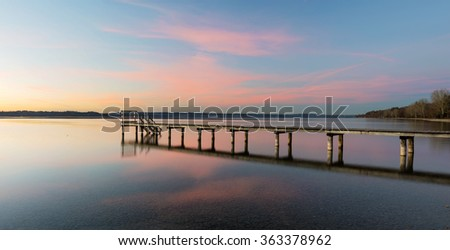 A wooden jetty at sunset at Lake Starnberger See with colorful sky and reflection, Buchscharn, Seeshaupt, Bavaria, Germany