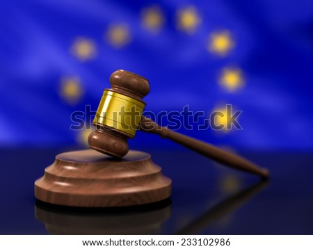 A Wooden Judge Gavel in Focus and Flag of European Union Waving in Background - stock photo