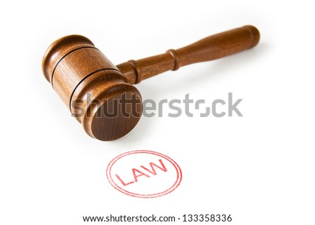 A wooden Judge's gavel with a red Law stamp against a white background - stock photo