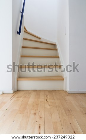 A wooden ladder leading up through white walls - stock photo