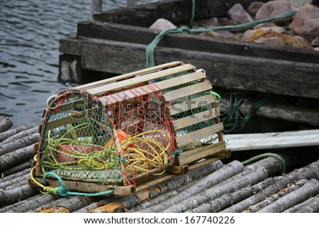 A wooden lobster trap with buoys and rope on a Newfoundland, Canada wharf. - stock photo