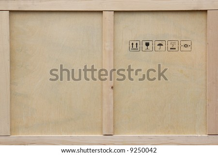 A wooden packing crate with various packing symbols. - stock photo
