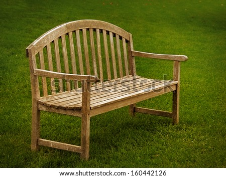 A wooden park bench with green grass. - stock photo