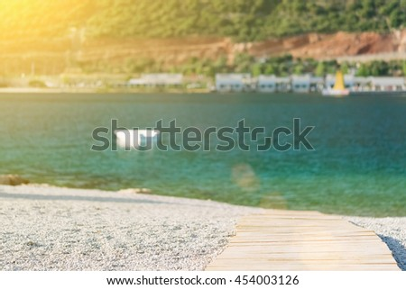 A wooden path leads to the sea at sunrise - stock photo